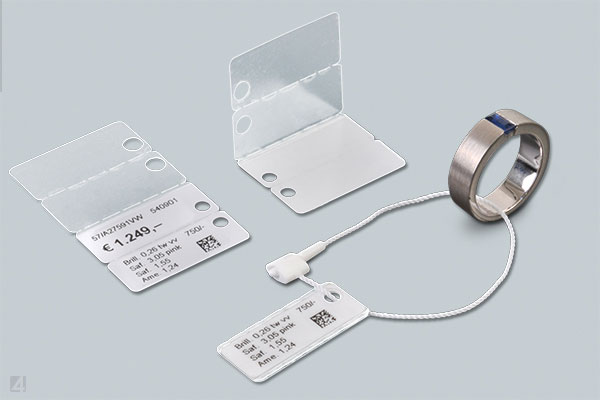 Application of security threads for self-adhesive WrapTag jewellery labels